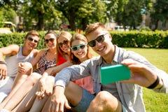Amis de sourire avec le smartphone faisant le selfie Photo stock