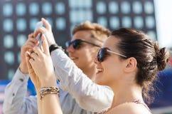 Amis de sourire avec le smartphone prenant la photo Photographie stock