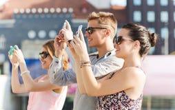 Amis de sourire avec le smartphone prenant la photo Images libres de droits
