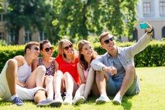 Amis de sourire avec le smartphone se reposant sur l'herbe Photos stock