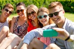 Amis de sourire avec le smartphone se reposant sur l'herbe Image libre de droits