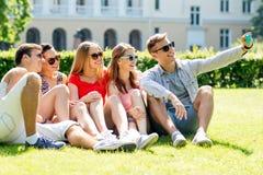 Amis de sourire avec le smartphone se reposant sur l'herbe Images libres de droits