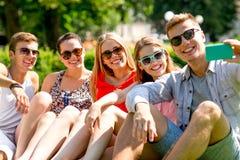 Amis de sourire avec le smartphone se reposant sur l'herbe Photographie stock libre de droits