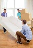 Amis de sourire avec le sofa et les boîtes à la nouvelle maison Photographie stock libre de droits