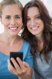 Amis de sourire avec le téléphone portable Photo stock