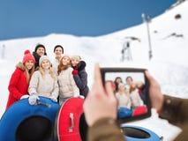 Amis de sourire avec les tubes de neige et le PC de comprimé Photos libres de droits