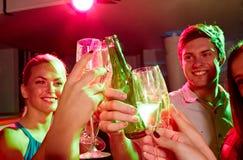 Amis de sourire avec les verres et la bière de vin dans le club Photo stock