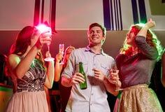 Amis de sourire avec les verres et la bière de vin dans le club Photographie stock libre de droits