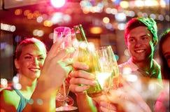 Amis de sourire avec les verres et la bière de vin dans le club Image stock