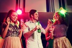 Amis de sourire avec les verres et la bière de vin dans le club Photographie stock