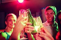 Amis de sourire avec les verres et la bière de vin dans le club Photos stock