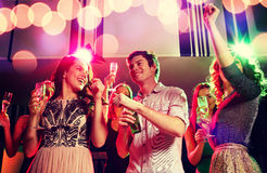 Amis de sourire avec les verres et la bière de vin dans le club Images stock