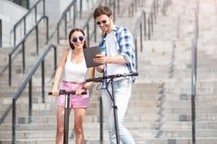 Amis de sourire avec plaisir à l'aide des scooters Photo stock
