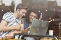 Amis de sourire avec une boisson chaude utilisant l'ordinateur portable Images libres de droits