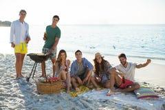 Amis de sourire ayant des boissons par le barbecue à la plage Images libres de droits