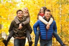 Amis de sourire ayant l'amusement dans le parc d'automne Photographie stock libre de droits