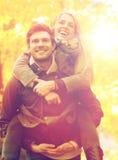 Amis de sourire ayant l'amusement dans le parc d'automne Photos libres de droits