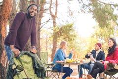 Amis de sourire ayant l'amusement dans le terrain de camping Images stock