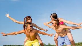 Amis de sourire ayant l'amusement sur la plage d'été Photo libre de droits