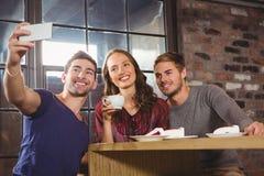 Amis de sourire ayant le café et prendre des selfies Photographie stock libre de droits