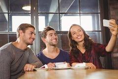 Amis de sourire ayant le café et prendre des selfies Photos stock