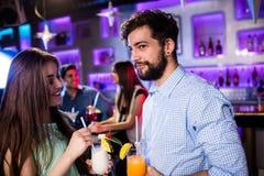 Amis de sourire ayant le cocktail au compteur de barre Image stock