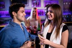 Amis de sourire ayant le verre de bière et de vin au compteur de barre Photographie stock
