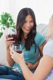 Amis de sourire ayant le vin rouge ensemble Photos stock