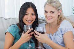 Amis de sourire ayant le vin rouge regardant ensemble l'appareil-photo Photos stock