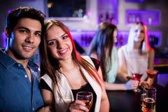 Amis de sourire ayant un verre de vin dans la barre Photos stock