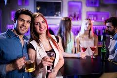 Amis de sourire ayant un verre de vin et de bière dans la barre Photos libres de droits