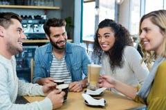 Amis de sourire ayant une tasse de café et de café froid dans le café Photo libre de droits
