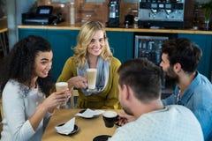 Amis de sourire ayant une tasse de café et de café froid dans le café Photographie stock