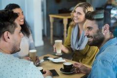 Amis de sourire ayant une tasse de café et de café froid dans le café Photos stock