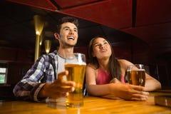 Amis de sourire buvant de la bière ensemble Photo stock