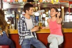 Amis de sourire buvant de la bière ensemble Photographie stock