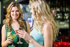 Amis de sourire buvant des cocktails Image stock