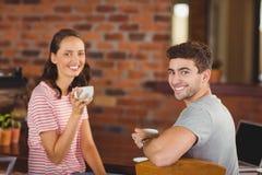 Amis de sourire buvant du café Images stock