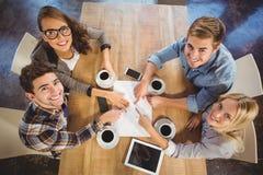 Amis de sourire buvant du café et se dirigeant sur le papier Images libres de droits