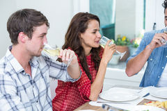 Amis de sourire buvant du vin blanc Image stock