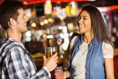 Amis de sourire buvant la bière et le cocktail Photographie stock