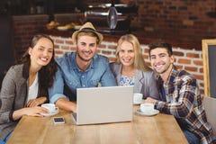 Amis de sourire buvant le café et à l'aide de l'ordinateur portable Images libres de droits