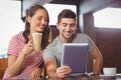 Amis de sourire buvant le café et regarder la tablette Photo stock