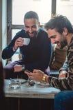 Amis de sourire buvant le café et regarder le téléphone portable Photographie stock libre de droits