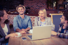 Amis de sourire buvant le café et rire Image stock