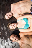 Amis de sourire détendant sur la plate-forme en bois Image libre de droits