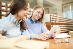 Amis de sourire d'étudiant lisant l'article en ligne dans la bibliothèque Photos stock