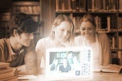 Amis de sourire d'université observant des photos sur l'interface numérique Images libres de droits