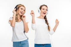 Amis de sourire dans des écouteurs Photos stock