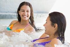 Amis de sourire dans des bikinis détendant dans le baquet chaud Photographie stock